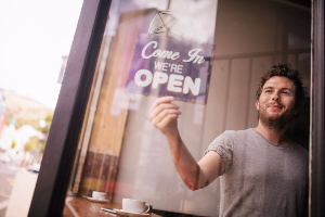 Man turning Open sign over in business window