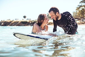 Couple in ocean on surfboard