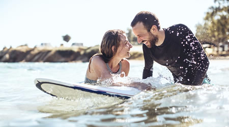 A couple in the water, laughing on a surfboard