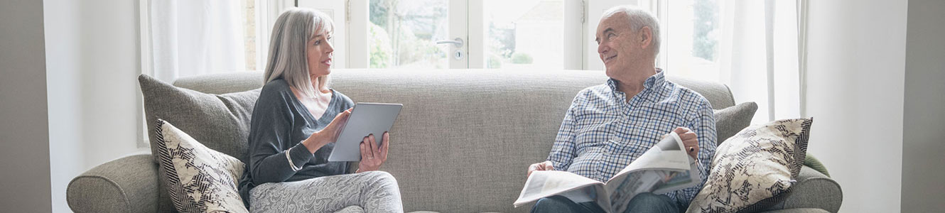 Senior couple at home reading paper and on tablet